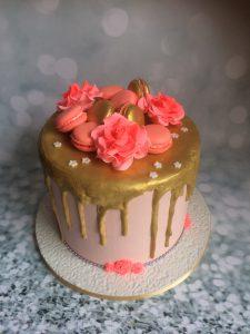 Creme driptaart met macarons en rozen